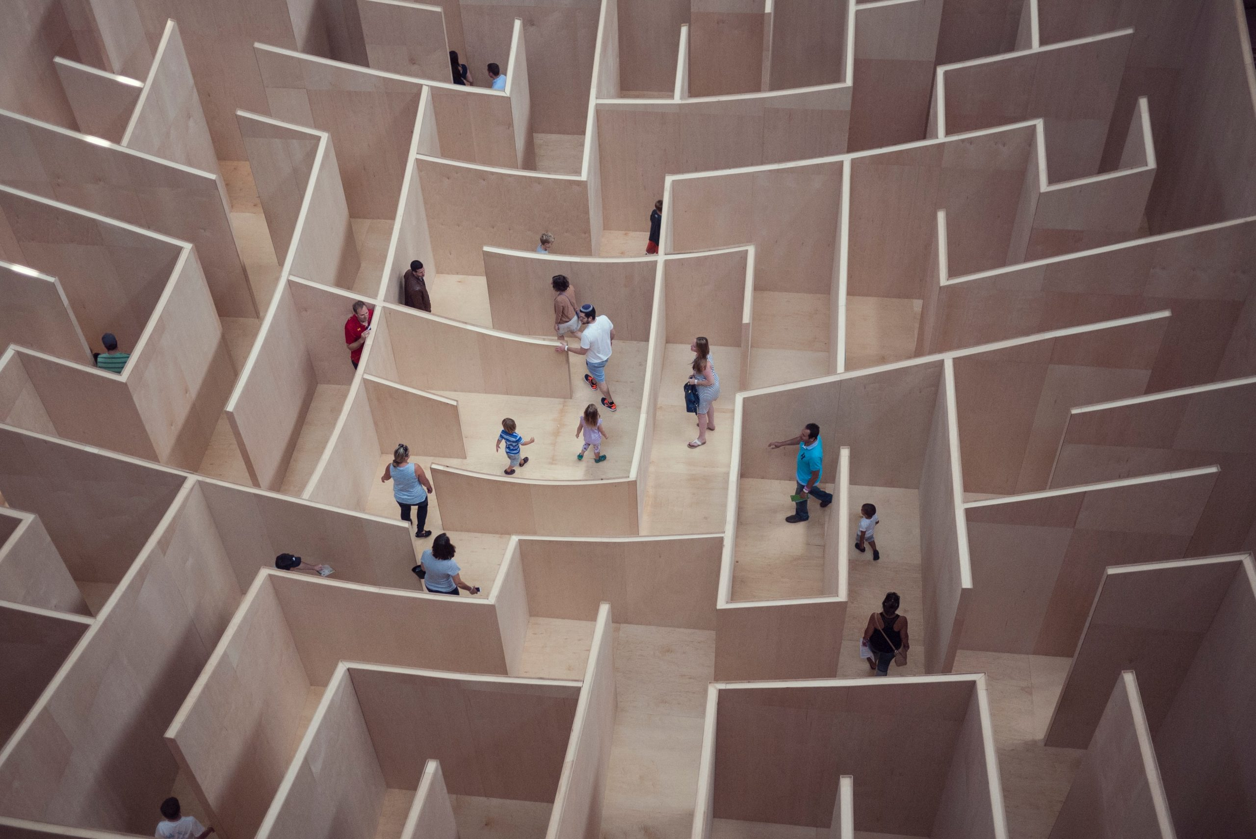 People trying to find their way through a wooden maze