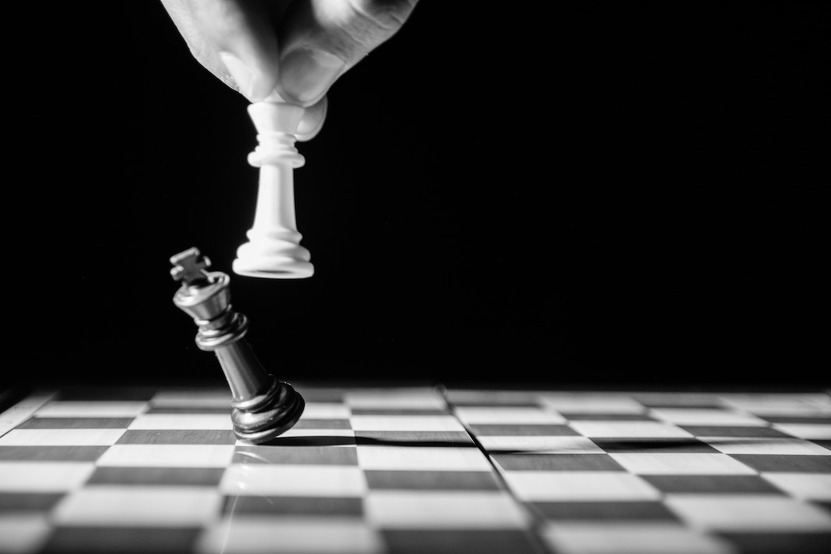 Hand holding a white chess piece capturing a black chess piece